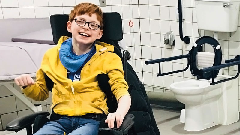 Smiling boy in wheelchair, inside a Changing Places facility